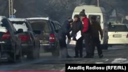Qırğızıstan, qarlı havada uşaqlar yol kənarında durub sürücülərə elanlar paylayırlar, fevral 2017