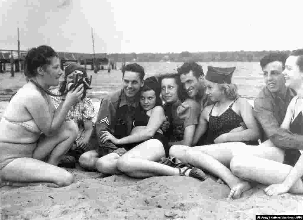 "American troops with German girls at Berlin's Wansee lake in July 1945, shortly after the Americans arrived in the city. Such fraternizing with well-supplied ex-enemies would have been scandalous but, as one woman at the time noted, ""first comes food, then comes morals."""