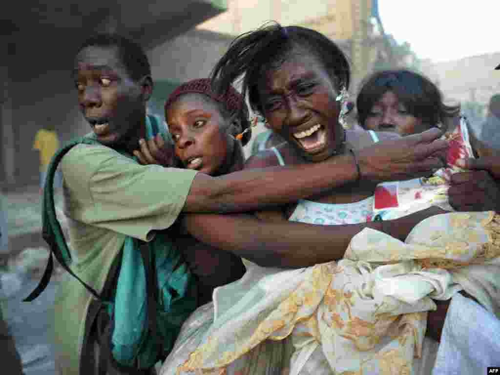 Вулічная гандлярка ў Порт-о-Прэнсе бароніць свой тавар ад рабаўнікоў - Фота: AFP