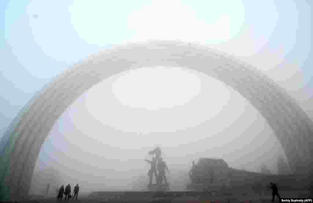Людзі ідуць у тумане міма манумэнта савецкіх часоў. Кіеў, Украіна.