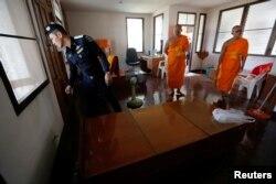 Полицейские во время обыска храмового комплекса Дхакаммая