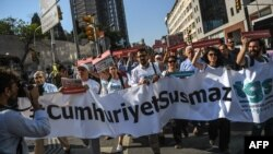 "Protesters hold a banner reading ""Cumhuriyet won't be silenced"" as they march in Istanbul on July 24."