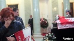 Жінка плаче біля трун покійного президента Леха Качиньського і його дружини Марії в президентському палаці у Варшаві, 13 квітня 2010 року