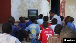 People sit around a television set to watch the opening game of the 2010 World Cup in Mogadishu