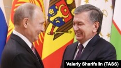 Russian President Vladimir Putin (left) welcomes his Uzbek counterpart, Shavkat Mirziyoev, before a CIS summit outside Moscow on December 26, 2017.
