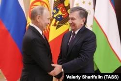 Mirziyoev met with Russian President Vladimir Putin (left) outside Moscow on December 26.