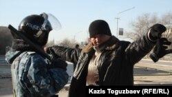 Жаңаөзен қаласы тұрғынын тексеріп тұрған полицей. 19 желтоқсан, 2011 жыл.