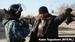 Полиция қызметкері жергілікті тұрғынды тексеріп тұр. Жаңаөзен, 19 желтоқсан 2011 жыл.