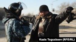 Полицей ер адамды тексеріп тұр. Жаңаөзен, 19 желтоқсан 2011 жыл. (Көрнекі сурет)
