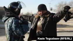Сотрудник полиции проверяет мужчину в городе Жанаозен Мангистауской области. 19 декабря 2011 года.