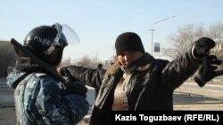 Полицей азаматты тексеріп тұр. Жаңаөзен, 19 желтоқсан 2011 жыл.
