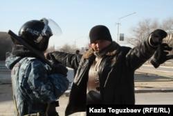 Сотрудник полиции проверяет мужчину в городе Жанаозен Мангистауской области, 19 декабря 2011 года.