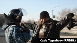 Төтенше жағдай тәртібіне сәйкес полицей қала тұрғынын тексеріп тұр. Жаңаөзен, 19 желтоқсан 2011 жыл.