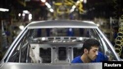 Сборка автомобиля на конвейере завода Iran Khodro. Тегеран, 20 июня 2011 года.