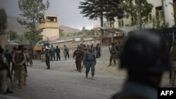 Afghan security personnel gather at the site of a suicide car bombing near Kabul on September 16.