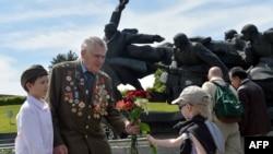 Хлопчик дарує ветеранові квіти біля пам'ятника воїнам Великої Вітчизняної війни у Києві, 9 травня 2014 року