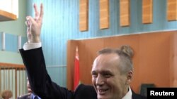 Former presidential candidate Uladzimir Nyaklyaeu flashes the victory sign before his court hearing.