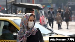 Iranians wear masks to help guard against dangerous levels of air pollution as they walk in the center of the smog-filled capital Tehran, November 13, 2019