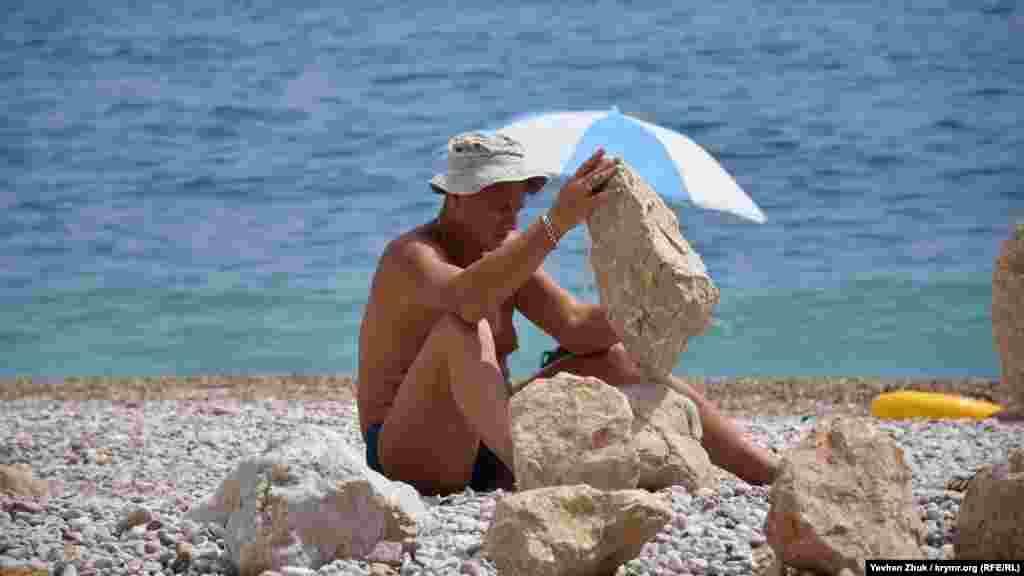 Здесь мужчина, отказавшийся представиться, устанавливает тяжелые камни один на другой. Это называется балансировкой камней