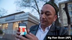 Омирбек Бикалы показывает фотографию своих родителей, которые, по его мнению, задержаны в Китае.