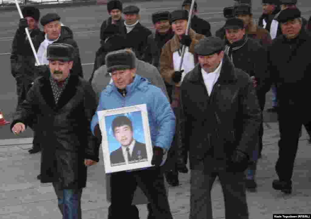 Жители Алматы идут к монументу Независимости, один из них держит в руках фотографию участника Декабрьских событий. 17 декабря 2011 года.