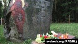 Кветкі і сьвечкі каля валуна «Ахвярам сталінізму»