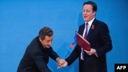 საფრანგეთის პრეზიდენტი ნიკოლა სარკოზი და ბრიტანეთის პრემიერ-მინისტრი დევიდ კამერონი ხელშეკრულების გაფორმების დროს