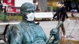 Amid a global coronavirus pandemic, a protective mask is placed on a statue in the Russian-occupied Ukrainian peninsula of Crimea.