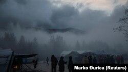 Migrants stand in fog inside Vucjak camp near Bihac