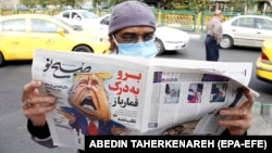 "A man reads a copy of Iranian daily newspaper Sobhe Nou with a cartoon depicting U.S. President Donald Trump and a headline reading ""Go to hell gambler"" in Tehran on November 7."