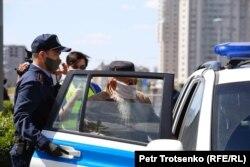 Полиция Тәуелсіздік алаңы маңынан ұстаған адамды көлікке салып әкеткелі жатыр. Нұр-Сұлтан, 6 маусым 2020 жыл.