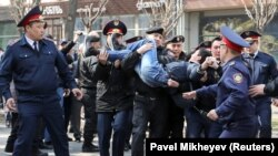 Kazakh police officers detain an anti-government protester during a rally in Almaty on March 22.