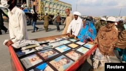 Relatives display pictures of people who have gone missing in restive province of Balochistan.