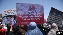 Afghan women hold up placards of Farkhunda Malikzada during a protest in Kabul in July 2015.