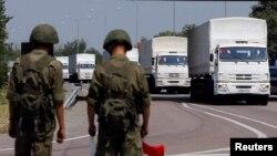 Российские солдаты наблюдают за грузовиками, движущимися к Украине. Недалеко от Новошахтинска Ростовской области. 14 августа 2014 года.
