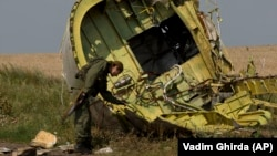 A Russia-backed separatist inspects the wreckage of Flight MH17 in eastern Ukraine on July 22, 2014.