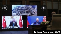 Turkish Recep Tayyip Erdogan (left) and Russian President Vladimir Putin speak during a ceremony as they remotely inaugurate construction at Turkey's Akkuyu power plant on March 10.