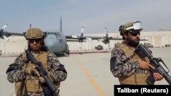 Членовите на воената единица Бадри 313 чуваат стража додека талибанскиот портпарол Забихула Муџахид ги изнесува своите забелешки на аеродромот во Кабул, 31 август 2021 година