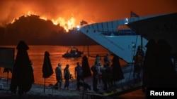 Njerëzit evakuohen përmes një trageti pasi një zjarr i madh përfshiu ishullin Evia, Greqi, 6 gusht 2021.