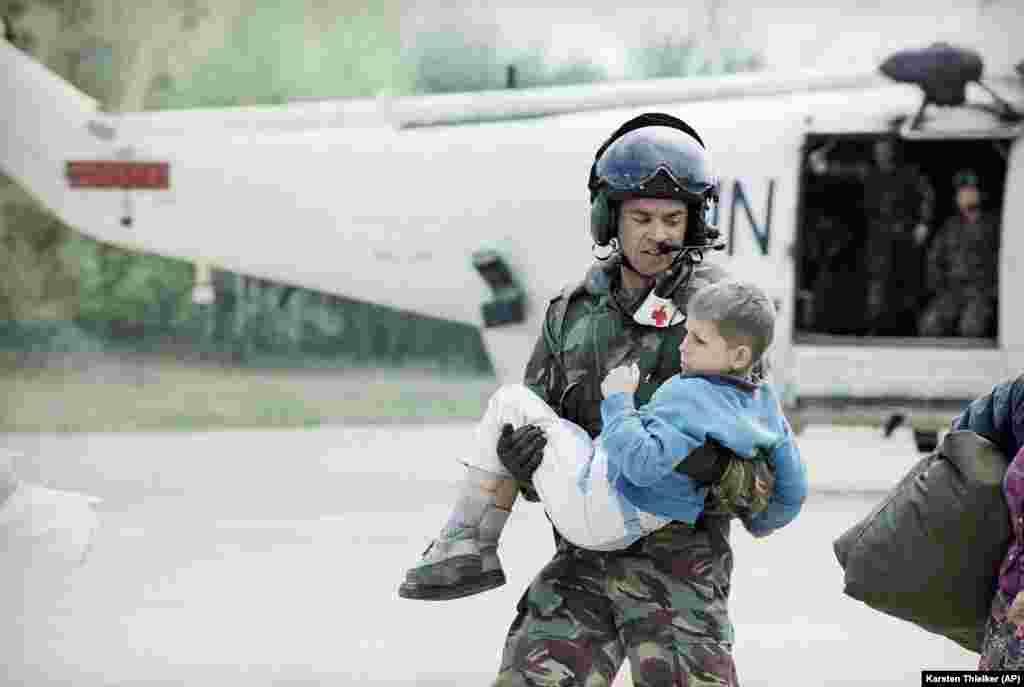 Французский пилот несет мальчика, эвакуированного из Сребреницы, в машину скорой помощи в аэропорту. Тузла, 25 апреля 1993 года.