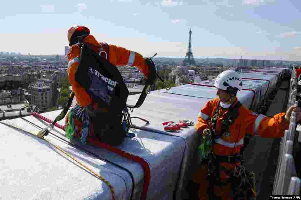 Muncitori urcați pe vârful Arcului de Triumf folosesc frânghia roșie pentru a fixa țesătura. Cele mai mari role de țesătură au o lățime de 8 metri și cântăresc în jur de o tonă.