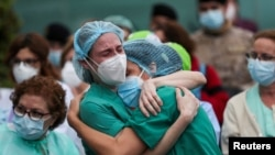 Медицинские работники в защитных масках реагируют на память о своем коллеге Эстебане, медсестре, умершей от осложнений, связанных с COVID-19, возле больницы Северо-Очоа во время вспышки коронавирусной болезни (COVID-19) в Леганесе, Испания. , 13 апреля 2020 г.