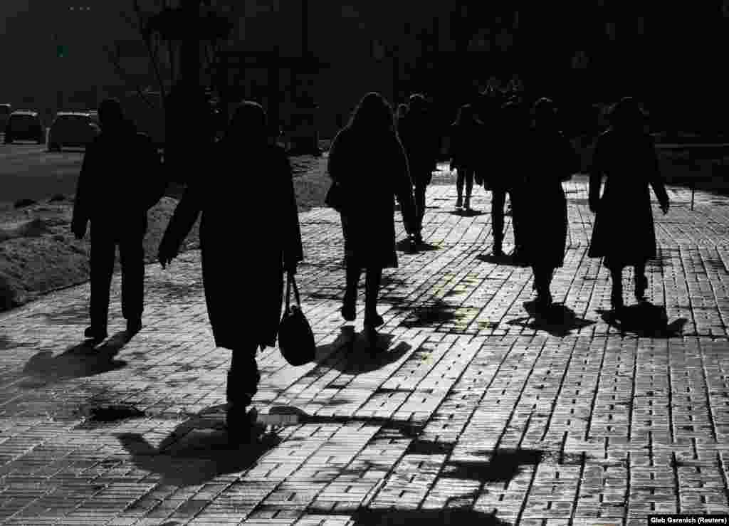 Pedestrians are silhouetted as they walk on the street during a sunny day in central Kyiv. (Reuters/Gleb Garanich)