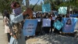 AFGHANISTAN -- A Taliban fighter (L) stands guard as Afghan women take part in an anti-Pakistan protest in Kabul, September 8, 2021