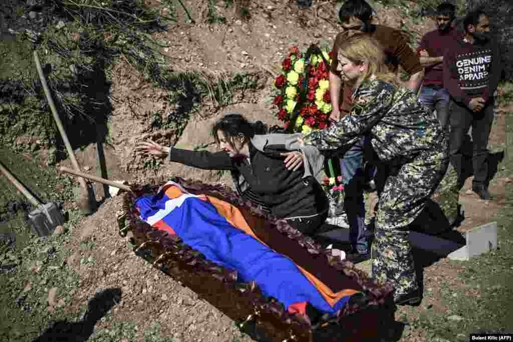 Мать оплакивает своего сына, тело которого завернуто в материю в цветах флага Нагорного Карабаха. Степанакерт, 17 октября 2020 года. Весь мир считает Карабах азербайджанской территорией, регион населен в основном этническими армянами.