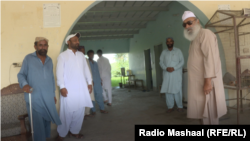 Mian Abdul Haq, widely known as Mian Mitha (right), strolls around his residence among his followers.