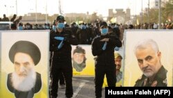 IRAQ -- Members of the Hashed al-Shaabi (Popular Mobilisation) paramilitary force stand near portraits of Iraq's top Shiite cleric Grand Ayatollah Ali Sistani (L) and slain Iranian general Qasem Soleimani (R) during a military parade in the southern Iraqi