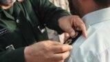 حسن شاهوارپور، فرمانده سپاه استانی خوزستان در حال قراردادن نشان نظامی بر شانه یکی از افسران نیروی انتظامی در ۱۵ مهر ۹۶