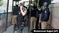 Pakistani police officers gather at a district court in Peshawar following the fatal shooting of a man accused of blasphemy on July 29.