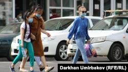 Пешеходы в защитных масках пересекают улицу.